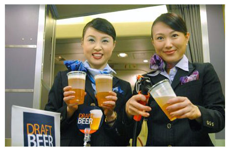 ANA flight attendants demonstrate new draft beer keg tap for in-flight beer