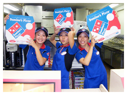 Female Domino's Japan employees hold pizza boxes at outlet in Japan.