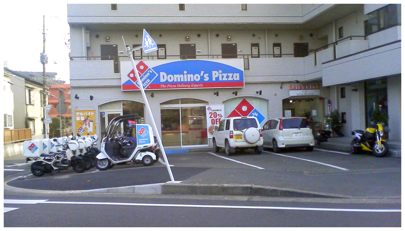Delivery scooter motor bikes in fron tof Domino's pizza outlet in Japan