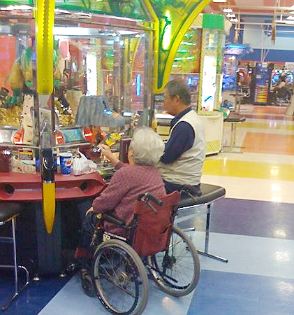 Elderly play medal game in Japan arcade game center
