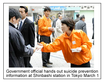 Japanese government official hands out suicide prevention tissue packs attrain  station in Tokyo