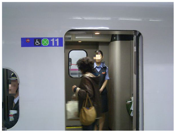 Attendant in bullet train green first class car in Japan