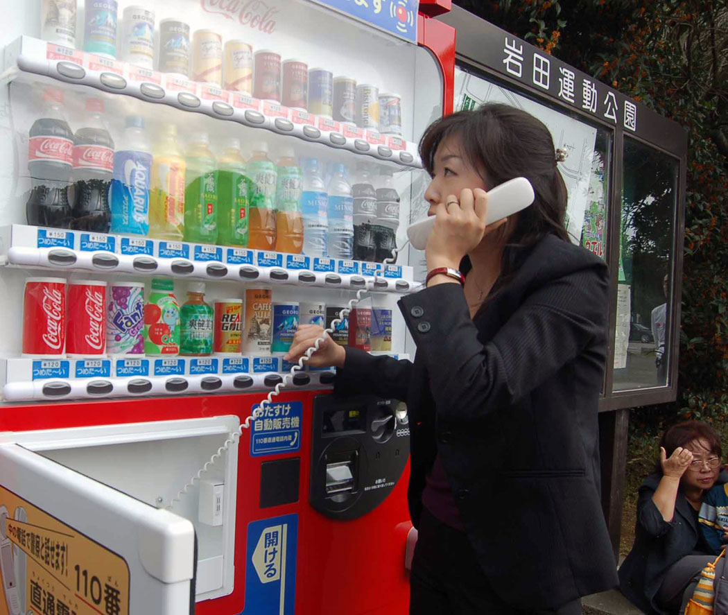 A woman test the Coca Cola emergency vending machine phone in Japan